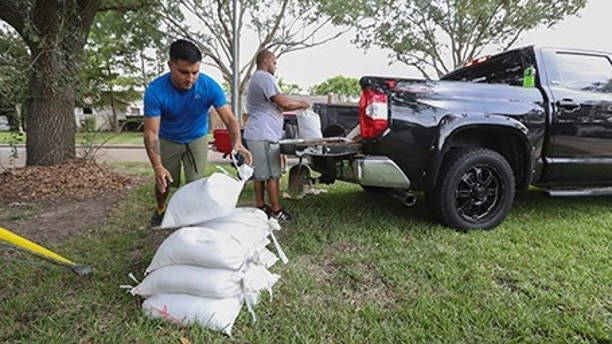 Albert Martinez and Victor Valerio fill bags with dirt from a pickup Thursday, Aug. 24, 2017, in Houston. Tropical Storm Harvey intensified Thursday into a hurricane that forecasters said would be the first major hurricane to hit Texas in 12 years. (Steve Gonzales/Houston Chronicle via AP)