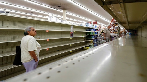 Shoppers pass empty shelves along the bottled water aisle in a Houston grocery store as Hurricane Harvey intensifies in the Gulf of Mexico, Thursday, Aug. 24, 2017. Harvey is forecast to be a major hurricane when it makes landfall along the middle Texas coastline. (AP Photo/David J. Phillip)