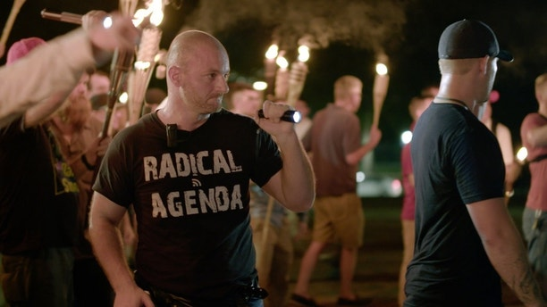 "ADDS ID: In this Friday, Aug. 11, 2017, image made from a video provided by Vice News Tonight, Christopher Cantwell attends a white nationalist rally in Charlottesville, Va. For all the words flowing since last weekend in Charlottesville, the most striking television reporting has been Vice Media's insider account of the white nationalist movement and what it has wrought. Correspondent Elle Reeve's initial story of the weekend violence took up the entirety of HBO's half-hour ""Vice News Tonight"" broadcast Monday, Aug. 14, and by Thursday had been viewed more than 36 million times on TV and online. (Vice News Tonight via AP)"