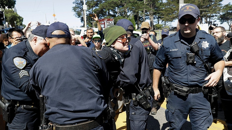 San Francisco Police officers arrest a protester outside of Alamo Square Park Saturday.