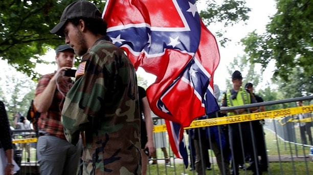 A white nationalist carries the Confederate flag as he arrives for a rally in Charlottesville, Virginia, U.S., August 12, 2017.   REUTERS/Joshua Roberts - RTS1BI7C
