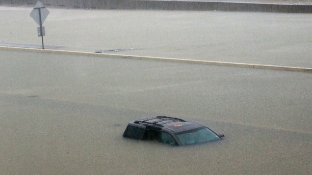 An abandoned vehicle sits in flood waters on the I-10 highway in Houston,