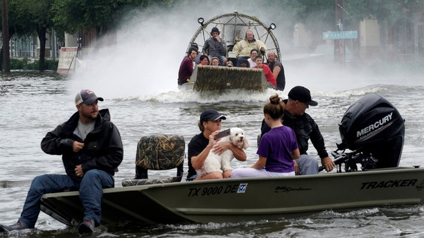 People are rescued from flood waters from Hurricane Harvey on an air boat in Dickinson, Texas August 27, 2017. REUTERS/Rick Wilking - RTX3DKR1
