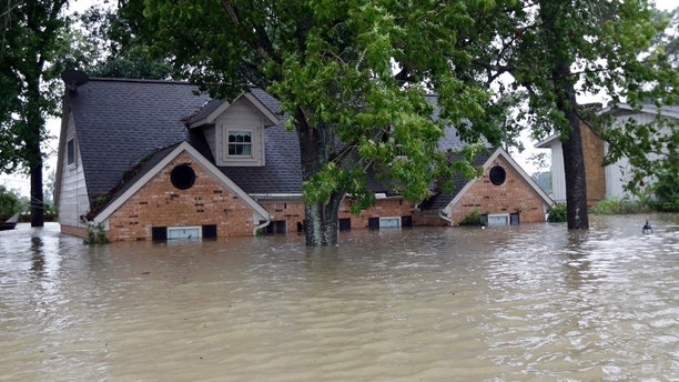 A home is surrounded by floodwaters from Tropical Storm Harvey on Monday, Aug. 28, 2017, in Spring, Texas. (AP Photo/David J. Phillip)