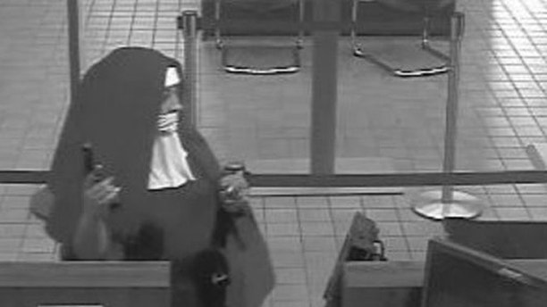 Two armed robbers dressed as nuns flee after a failed bank heist