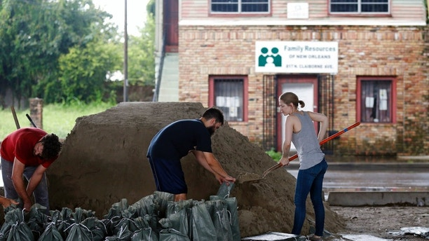 Andrea Dube, right, and John Flemming fill sandbags as a precaution for the potential of more flooding from rain storms, in New Orleans, Friday, Aug. 11, 2017. With debris from last weekend's flash flood still piled up on sidewalks and their city under a state of emergency, New Orleans residents looked ahead warily on Friday to the prospect of more rain to tax the city's malfunctioning pump system. (AP Photo/Gerald Herbert)