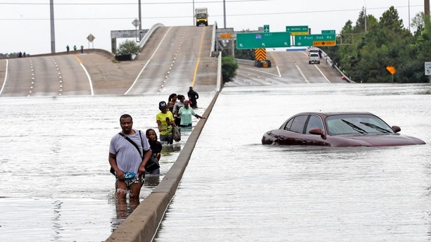 Evacuees wade down a flooded section of Interstate 610 as floodwaters from Tropical Storm Harvey rise Sunday, Aug. 27, 2017, in Houston. The remnants of Hurricane Harvey sent devastating floods pouring into Houston Sunday as rising water chased thousands of people to rooftops or higher ground. (AP Photo/David J. Phillip)