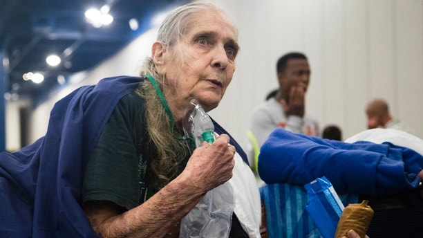 Theresa Ross receives a tank of oxygen when she arrived to the George R. Brown Convention Center seeking shelter with her husband in Houston on Monday, Aug. 28, 2017. Floodwaters reached the rooflines of single-story homes Monday and people could be heard pleading for help from inside as Harvey poured rain on the Houston area for a fourth consecutive day after a chaotic weekend of rising water and rescues. (Marie D. De Jesus/Houston Chronicle via AP)