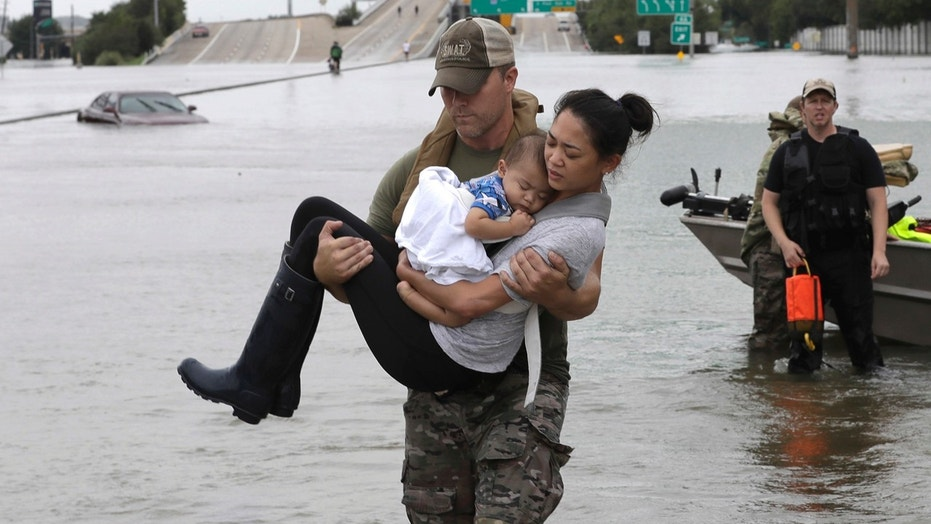Aug. 27: Houston Police SWAT officer Daryl Hudeck carries Catherine Pham and her 13-month-old son Aiden after rescuing them from their home surrounded by floodwaters from Tropical Storm Harvey