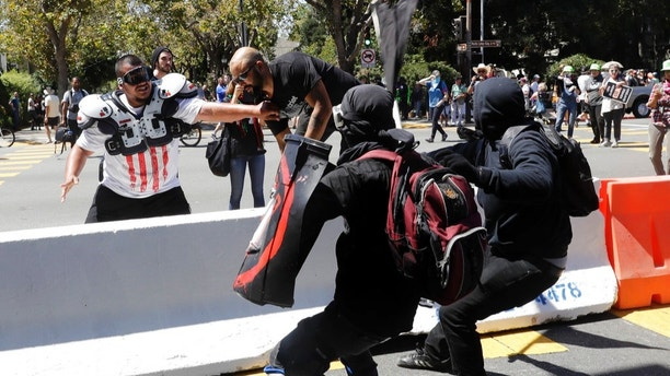 "Demonstrator Joey Gibson, second from left, is chased by anti-fascists during a free speech rally Sunday, Aug. 27, 2017, in Berkeley, Calif. Several thousand people converged in Berkeley Sunday for a ""Rally Against Hate"" in response to a planned right-wing protest that raised concerns of violence and triggered a massive police presence. Several people were arrested for violating rules against covering their faces or carrying items banned by authorities. (AP Photo/Marcio Jose Sanchez)"