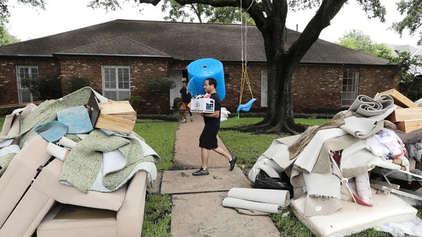 Michael Saghian carries a roll of bubble wrap and a box of sandwiches for workers helping remove items damaged by floodwaters from Tropical Storm Harvey from his home Wednesday, Aug. 30, 2017, in Houston. (AP Photo/David J. Phillip)