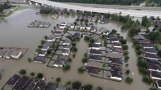 Homes are surrounded by floodwaters from Tropical Storm Harvey Tuesday, Aug. 29, 2017, in Spring, Texas. (AP Photo/David J. Phillip)
