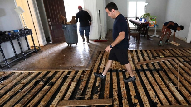 Michael Saghian walks across the living room of his home damaged by floodwaters from Tropical Storm Harvey on Wednesday, Aug. 30, 2017, in Houston. (AP Photo/David J. Phillip)
