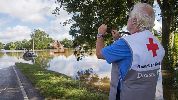 James Hennessy, a Red Cross mental health volunteer from Tallahassee, Florida, takes a photo of Old Jefferson Highway which he was hoping to cross to reach Baton Rouge in Prairieville, La., Tuesday, Aug. 16, 2016. (AP Photo/Max Becherer)