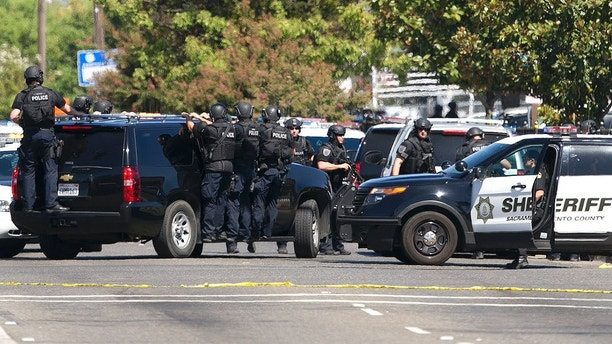 Law enforcement officers in tactical gear arrive at the scene were suspects believed to be involved in the shooting of three law enforcement officers, Wednesday, Aug. 30, 2017, in Sacramento, Calif. Authorities say two California Highway Patrol officers and one Sacramento County Sheriff's deputy were hospitalized are being shot during a vehicle theft investigation. One suspect was shot and hospitalized and two women were also taken into custody. (AP Photo/Rich Pedroncelli)