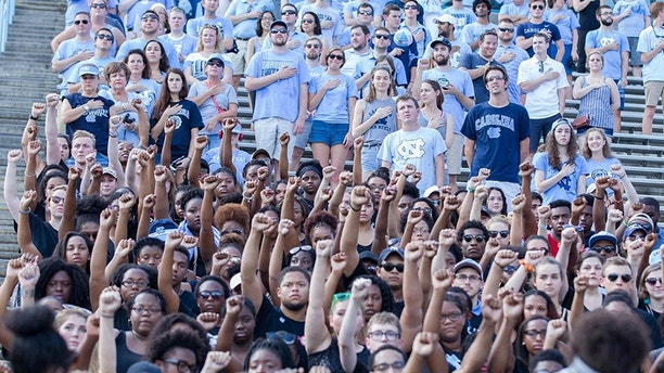 Sep 24, 2016; Chapel Hill, NC, USA;  North Carolina Tar Heels students hold up their fists during the national anthem in silent protest during the game against the Pittsburgh Panthers at Kenan Memorial Stadium. Mandatory Credit: Jeremy Brevard-USA TODAY Sports - 9561061