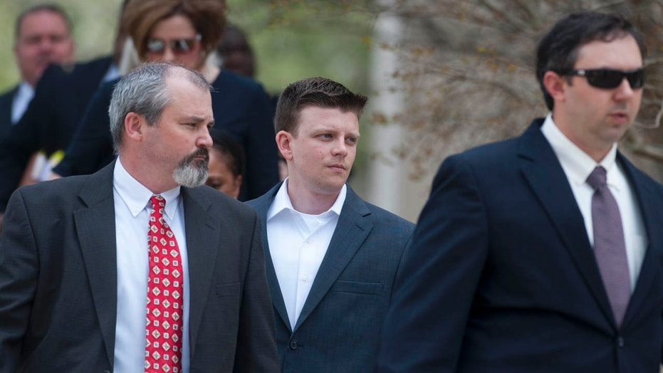 FILE- In this March 24, 2016 file photo, Montgomery Police Officer Aaron Smith, center, arrives for a hearing at the county courthouse in Montgomery, Ala.