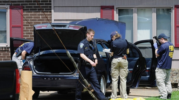 Law enforcement agents search a car at the home of reputed Connecticut mobster Robert Gentile in Manchester, Conn., Thursday, May 10, 2012. Gentile's lawyer A. Ryan McGuigan says the FBI warrant allows the use of ground-penetrating radar and believes they are looking for paintings stolen from Boston's Isabella Stewart Gardener Museum worth half a billion dollars. (AP Photo/Jessica Hill)