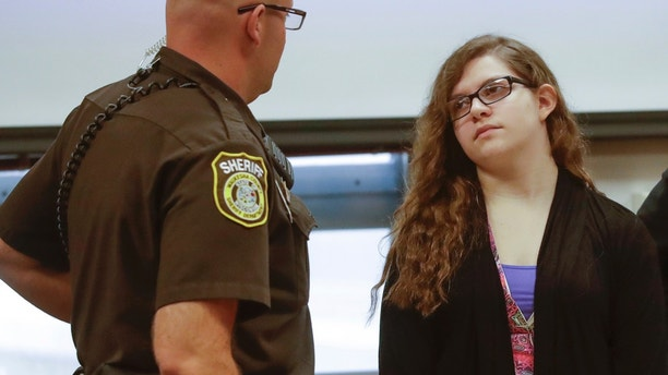 Anissa Weier talks to a sheriff's deputy during a pause in jury selection in the trial to determine 15-year-old Weier's competency at Waukesha County Courthouse Monday, Sept 11, 2017, in Waukesha, Wis. Prosecutors allege that Weier and her friend, Morgan Geyser, lured classmate Payton Leutner into a Waukesha park in May 2014 and stabbed her 19 times. The girls have said it was an effort to please a fictional horror character known as Slender Man.  (AP Photo/Morry Gash, Pool)