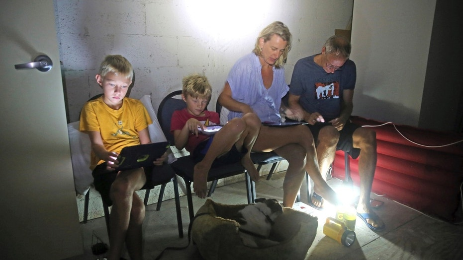 The Blinckman family use their personal devices while sheltering in a stairwell utility closet as Hurricane Irma hit Key West, Fla., Sept. 10, 2017.