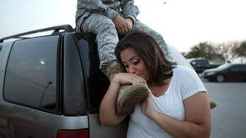 Lucy Hamlin leans on her husband's foot, Specialist Timothy Hamlin, as they wait to be allowed back onto Fort Hood, Texas, where they reside, Wednesday, April 2, 2014. An Iraq War veteran being treated for mental illness was the gunman who opened fire at Fort Hood, killing three people and wounding 16 others before committing suicide, in an attack on the same Texas military base where more than a dozen people were slain in 2009, authorities said. (AP Photo/Austin American-Statesman, Deborah Cannon)