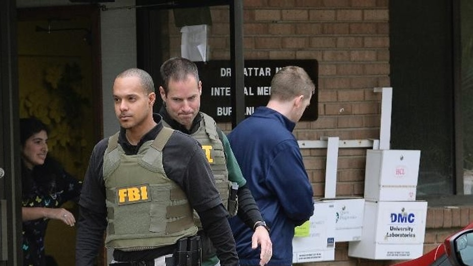 FBI agents leave the office of Dr. Fakhruddin Attar after completing a search for documents.