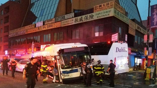 In this photo provided by the NYPD's 109th Precinct, officers respond to a collision involving two buses on Main Street in the Queens borough of New York, Monday, Sept. 18, 2017. The Fire Department of New York said several been hurt, some of them severely, when a city bus and a tour bus collided in the Flushing neighborhood. (NYPD's 109th Precinct via AP)