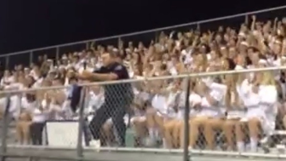 Officer Jack Taschner leads a cheer at a high school football game.