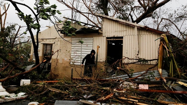 A man looks for valuables in the damaged house of a relative after the area was hit by Hurricane Maria in Guayama, Puerto Rico September 20, 2017. REUTERS/Carlos Garcia Rawlins     TPX IMAGES OF THE DAY - RC1736A452A0