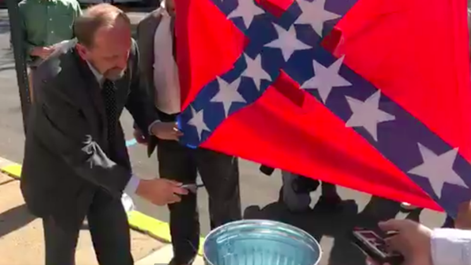 Activist Gene Stilp burns a hybrid Confederate/Nazi flag in front of the Columbia County courthouse to protest the Bloomsburg Fair allowing vendors to sell Confederate items.