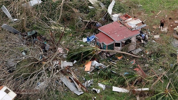 A man stands outside a destroyed home in this aerial photo from a Marine Corps MV-22 Osprey surveying the aftermath from Hurricane Maria in St. Croix, U.S. Virgin Islands September 21, 2017.  REUTERS/Jonathan Drake - RC1BCD434FE0