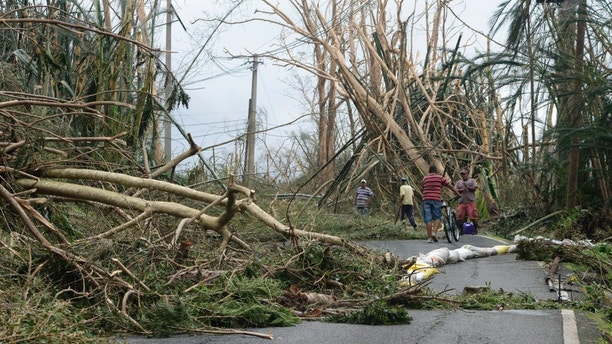 Locals help clear debris from a road after the passing of Hurricane Maria, in Yabucoa, Puerto Rico, Thursday, September 21, 2017. As of Thursday evening, Maria was moving off the northern coast of the Dominican Republic with winds of 120 mph (195 kph). The storm was expected to approach the Turks and Caicos Islands and the Bahamas late Thursday and early Friday. (AP Photo/Carlos Giusti)