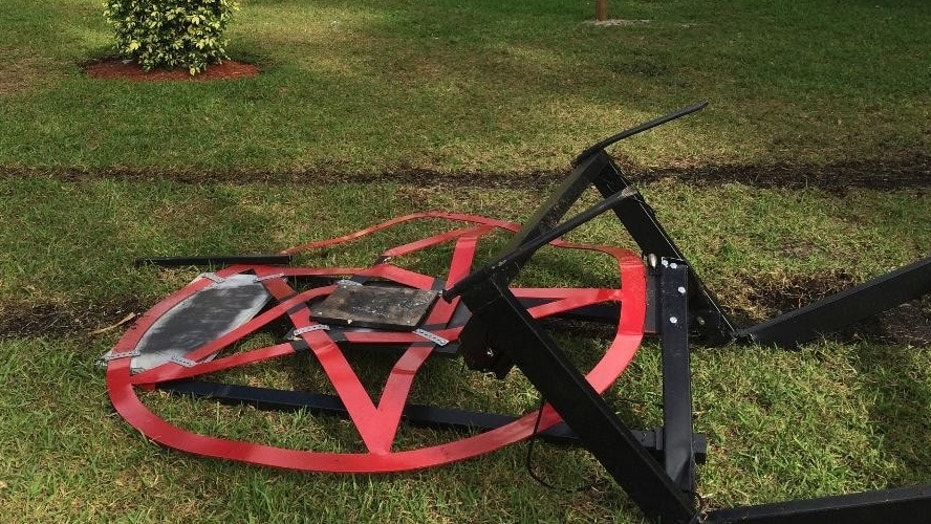A satanic pentagram erected by Preston Smith lies damaged .