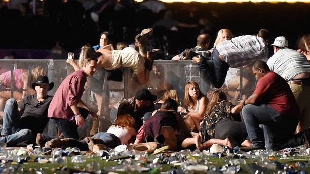 LAS VEGAS, NV - OCTOBER 01:  People scramble for shelter at the Route 91 Harvest country music festival after apparent gun fire was heard on October 1, 2017 in Las Vegas, Nevada. A gunman has opened fire on a music festival in Las Vegas, leaving at least 20 people dead and more than 100 injured. Police have confirmed that one suspect has been shot. The investigation is ongoing. (Photo by David Becker/Getty Images)
