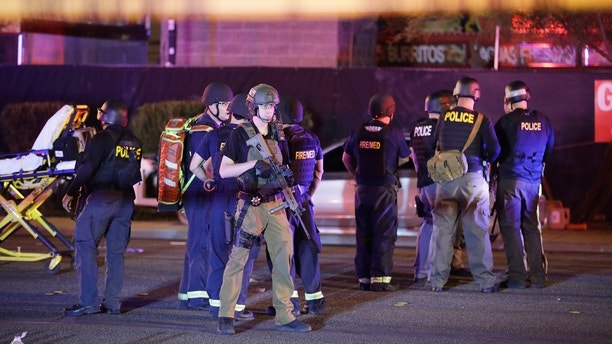 Police officers and medical personnel stand at the scene of a shooting near the Mandalay Bay resort and casino on the Las Vegas Strip, Monday, Oct. 2, 2017, in Las Vegas. Multiple victims were being transported to hospitals after a shooting late Sunday at a music festival on the Las Vegas Strip. (AP Photo/John Locher)
