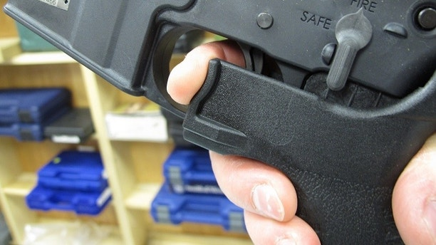 "FILE - In this Feb. 1, 2013, file photo, an employee of North Raleigh Guns demonstrates how a ""bump"" stock works at the Raleigh, N.C., shop. The gunman who unleashed hundreds of rounds of gunfire on a crowd of concertgoers in Las Vegas on Monday, Oct. 2, 2017, attached what is called a ""bump-stock"" to two of his weapons, in effect converting semiautomatic firearms into fully automatic ones. (AP Photo/Allen Breed, File)"