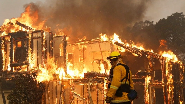 A firefighter monitors a house burning in Santa Rosa, Calif., Monday, Oct. 9, 2017.  Wildfires whipped by powerful winds swept through Northern California sending residents on a headlong flight to safety through smoke and flames as homes burned. (AP Photo/Jeff Chiu)