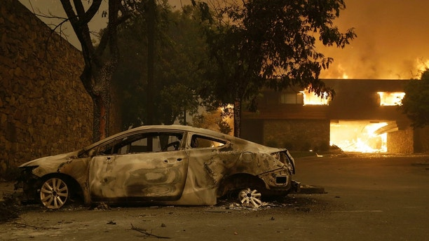 The remains of a car sits near the Fountaingrove Inn Hotel as it burns at rear in Santa Rosa, Calif., Monday, Oct. 9, 2017. (AP Photo/Jeff Chiu)