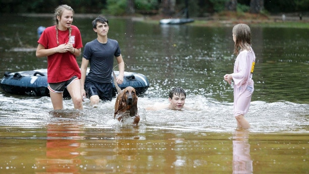 Crimson Peters, 7, right, Tracy Neilsen, 13, center right, Macee Neilsen, 15, left, and Tim Neilsen III, 16, center left, wade through the flood water the filled their front yard after Hurricane Nate, Sunday, Oct. 8, 2017, in Coden, Ala. (AP Photo/Brynn Anderson)