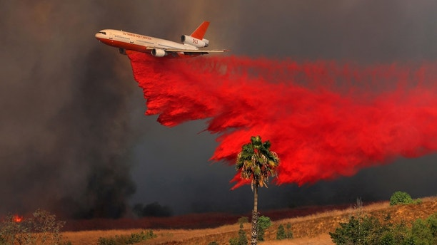 A DC-10 aircraft drops fire retardant on a wind driven wildfire in Orange, California, U.S., October 9, 2017.       REUTERS/Mike Blake - RC1D69477B40