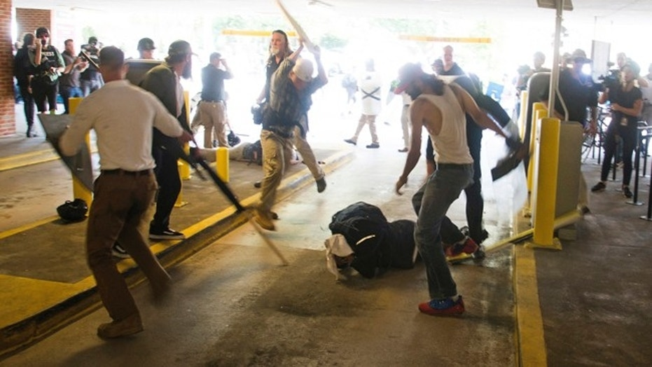 In this Saturday, Aug. 12, 2017 photo, DeAndre Harris, bottom is assaulted in a parking garage beside the Charlottesville police station after a white nationalist rally was disbursed by police, in Charlottesville, Va. (Zach D. Roberts via AP)