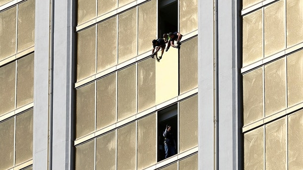 Workers board up a broken window at the Mandalay Bay hotel, where shooter Stephen Paddock conducted his mass shooting along the Las Vegas Strip, in Las Vegas, Nevada, U.S., October 6, 2017. REUTERS/Chris Wattie - RC17424B7F40