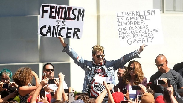 Conservative commentator Milo Yiannopoulos holds protest signs while speaking at the University of California in Berkeley, California, U.S., September 24, 2017. REUTERS/Noah Berger - RC1F9EBC0040