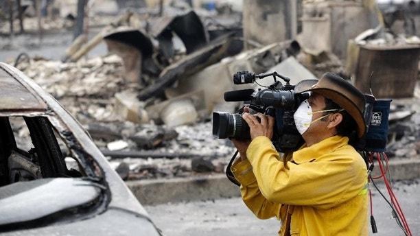 A video operator uses a mask as protetion against smoke and ash while filming the remains of an apartment building lost in a wildfire two days earlier, Monday, Sept. 14, 2015, in Middletown, Calif. Two of California's fastest-burning wildfires in decades overtook several Northern California towns, killing at least one person and destroying hundreds of homes and businesses and sending thousands of residents fleeing highways lined with buildings, guardrails and cars still in flames. (AP Photo/Elaine Thompson)
