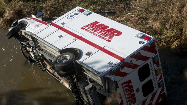An Mobile Medical Response ambulance rests in Misteguay Creek Monday, Oct. 16, 2017, after colliding with car on a bridge  in Maple Grove Township, Mich.  The driver of the car has died and two emergency workers are injured in the Monday crash.  (Jacob Hamilton/The Saginaw News via AP)