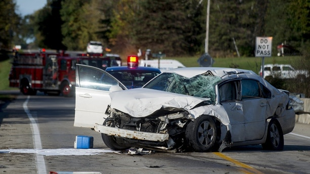 A car rests on a bridge Monday, Oct. 16, 2017, after colliding with a Mobile Medical Response ambulance in Maple Grove Township, Mich. The driver of the car has died and two emergency workers are injured in the Monday crash.  (Jacob Hamilton/The Saginaw News via AP)