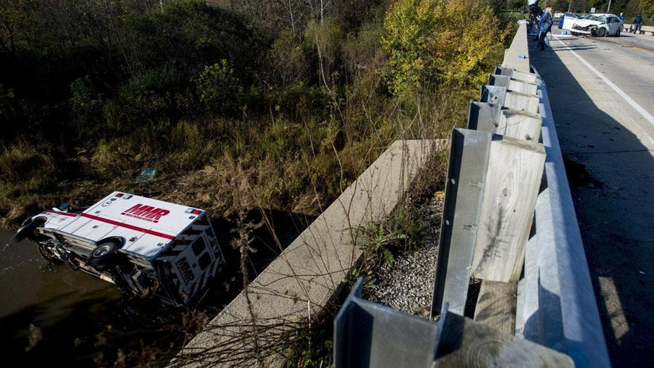 An Mobile Medical Response ambulance rests in Misteguay Creek Monday, Oct. 16, 2017, after colliding with a white Chevrolet Impala on a bridge in Maple Grove Township, Mich.