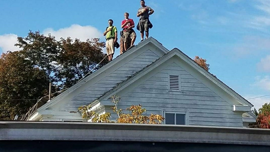 Roofers pause for national anthem played at nearby football game