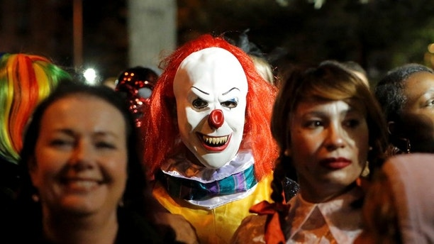 A person dressed in a clown costume stands amongst attendees during the Greenwich Village Halloween Parade in Manhattan, New York, U.S., October 31, 2016.  REUTERS/Andrew Kelly/File Photo - HT1ECCG128K18
