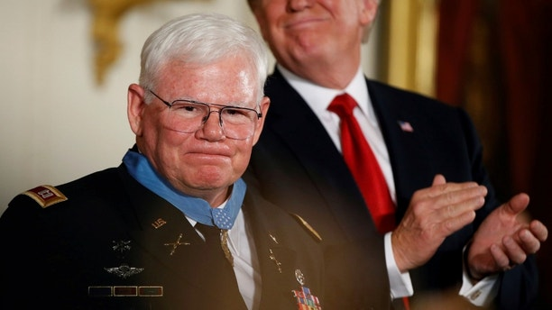 U.S. President Donald Trump claps after awarding the Medal of Honor to Vietnam War Veteran, retired Army Capt. Gary Rose (L), during a ceremony in the East Room of the White House in Washington, DC, U.S. October 23, 2017. REUTERS/Joshua Roberts - RC147FAB9A50